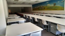 Photo of interior of wholesale vehicle dealer license location showing long rows of empty desks