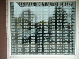 Photo of window sign at a wholesale vehicle dealer location showing 180 separate licensees
